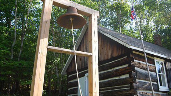 old schoolhouse bell in front of pioneer schoolhouse