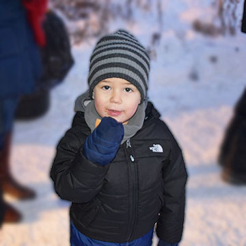 image of young child eating a cookie in the winter