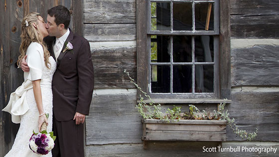 bride and groom kissing in front of log cabin
