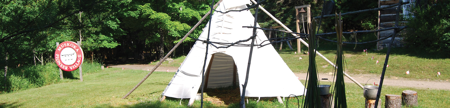 teepee in foreground, Muskoka Pioneer Village sign in background
