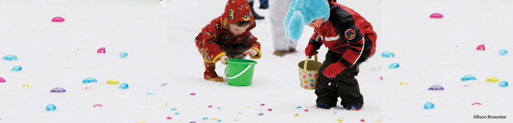 two children picking Easter eggs off a snowy ground