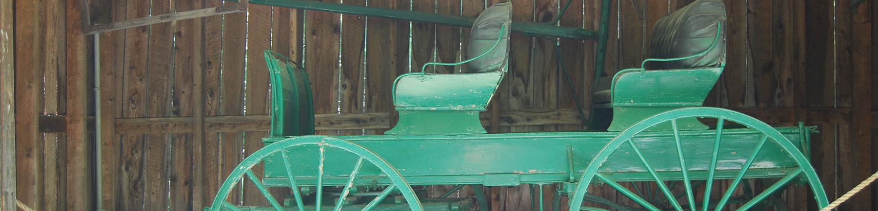 image of old green buggy with leather seats inside of a barn